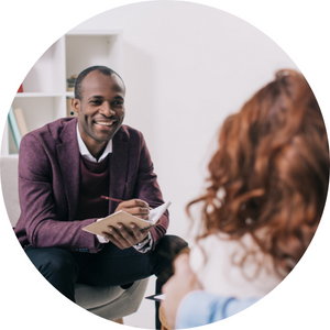 counselling services wollongong - image of man in dark coloured suit with notebook smiling at a women with long curly hair opposite him - call Direct Focus Solutions today