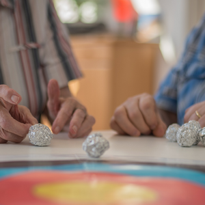 occupational therapy clinic - image of old persons hands flicking a ball of alfoil into a target on a table, beside younger set of hands - call DFS today