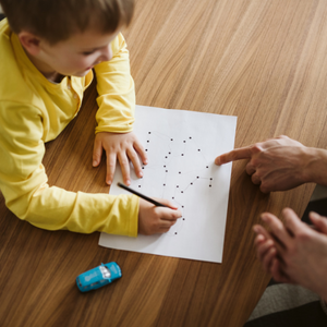 pediatric occupational therapist - young child in bright yellow long sleeve shirt connecting the dots on paper with blue toy car and adults hands pointing at paper - call DFS today