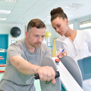private occupational therapy - image of man in grey shirt pedalling a machine with his hands and a women in a white shirt reviewing his movements - call DFS today